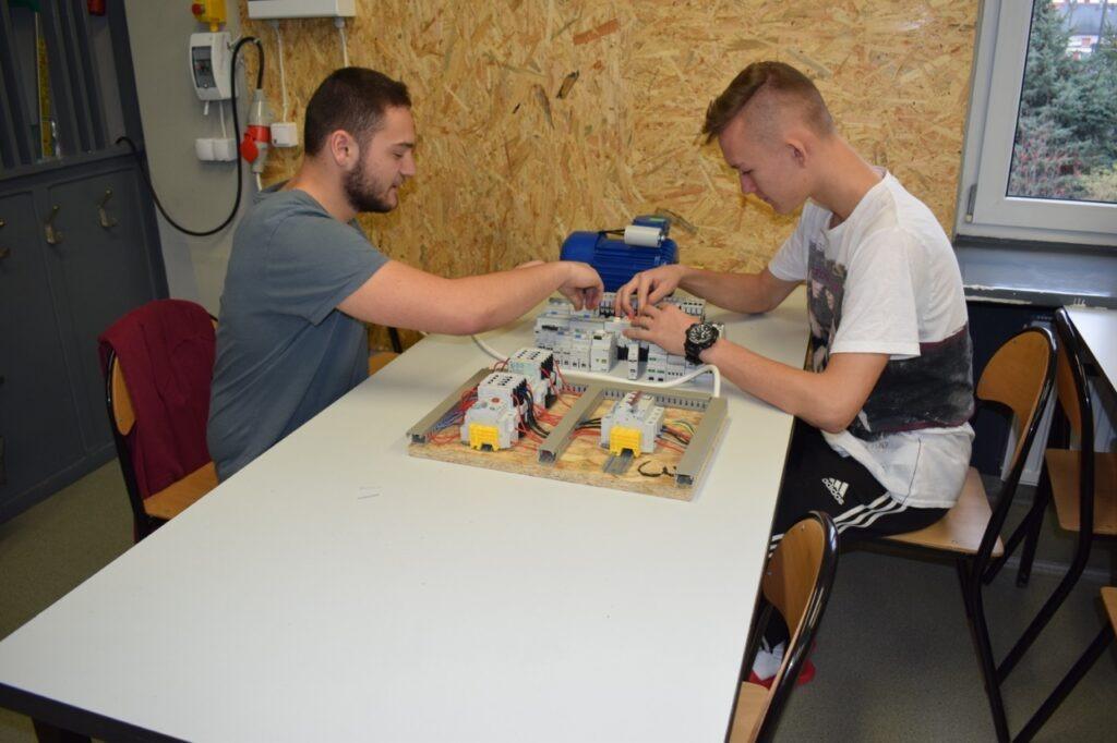Uczniowie montujący obwód elektryczny w pracowni