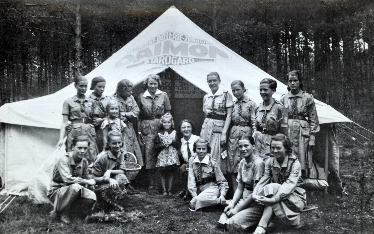 Czarno-biała fotografia harcerki przed namiotem