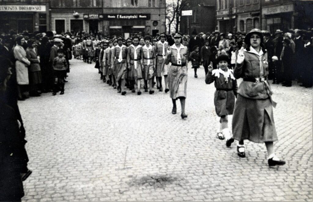 Czarno-biała fotografia harcerki maszerujące ulicą