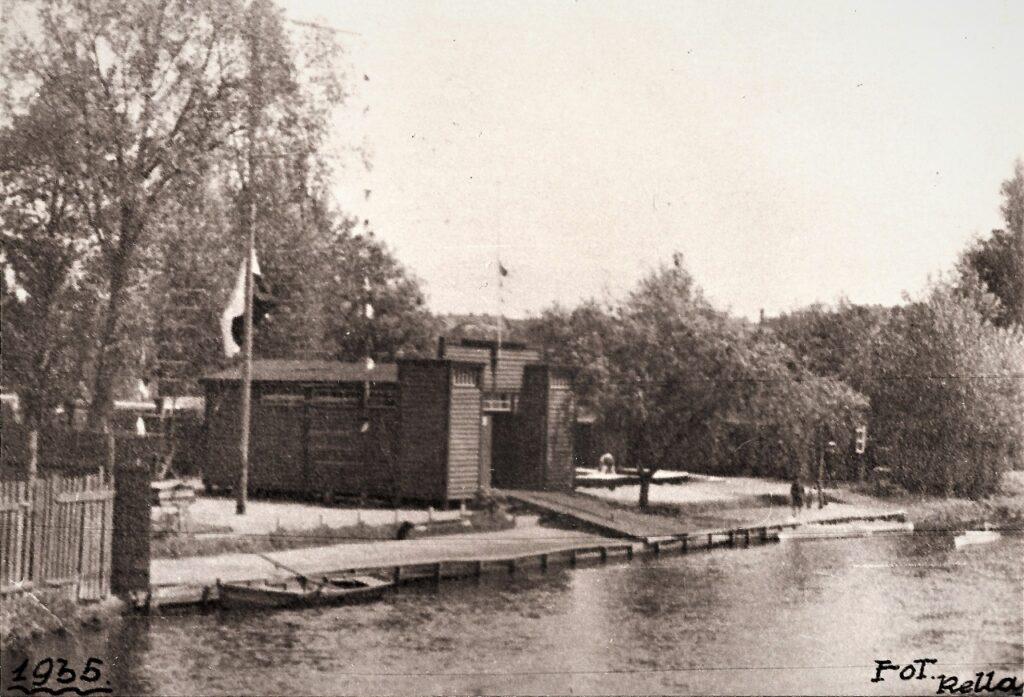 Czarno-biała fotografia wejście do obozu harcerskiego przypominające bramę zamku