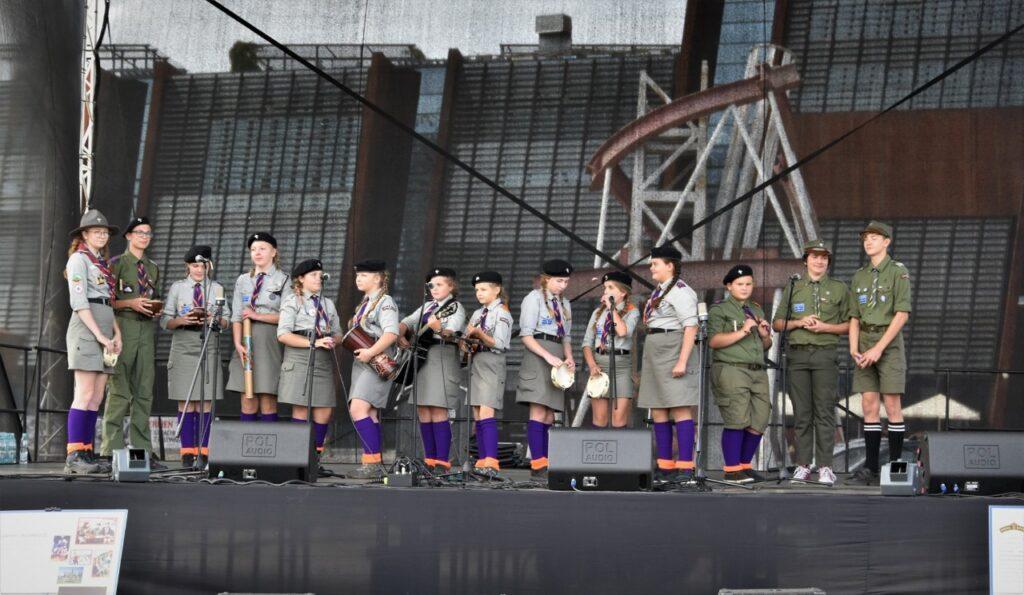 Harcerki i harcerze w czasie występu muzycznego na scenie