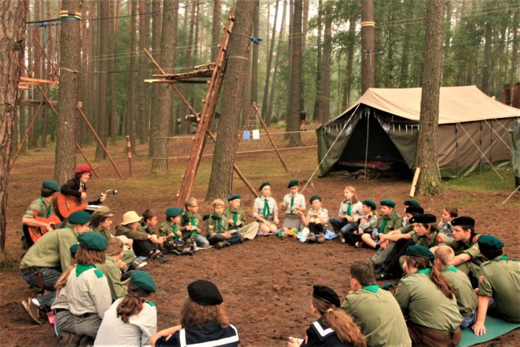 Harcerze i harcerskie siedzące w okręgu, w leśnym obozie