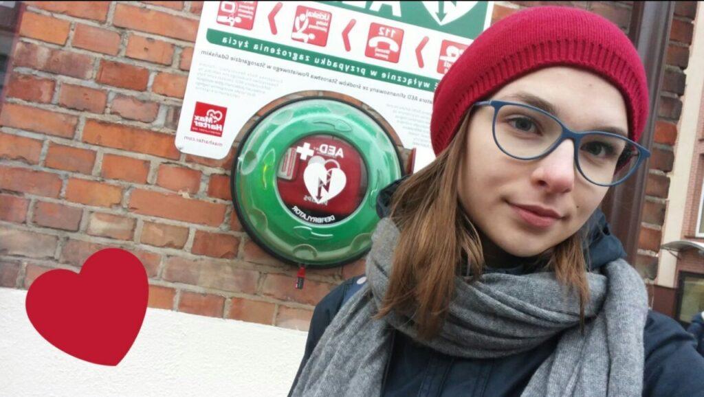 Zdjęcie osoby stojącej przy defibrylatorze zamontowanym na ścianie